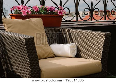 Brown cane-chair with the pillow on the roof