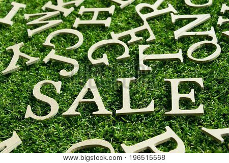 Wording sale on artificial green grass background with english alphabet as decoration