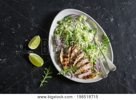Grilled chicken breast and cabbage peas and parmesan coleslaw. Healthy balanced food concept. On a dark background top view