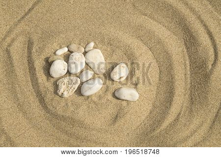 The group of the white pebbles on sand background