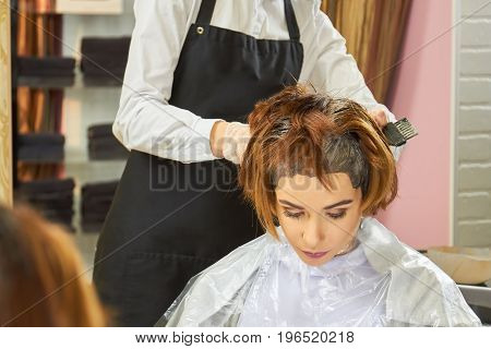 Beautician dying hair, female customer. Woman in a beauty salon.