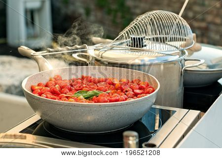 Sliced cherry tomatoes with basil cooking on a saucepan