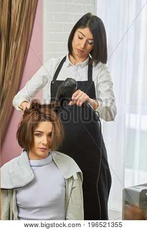 Hairdresser working with client. Woman using blow dryer.
