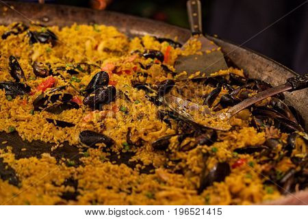 Large pan of seafood paella in a street tray