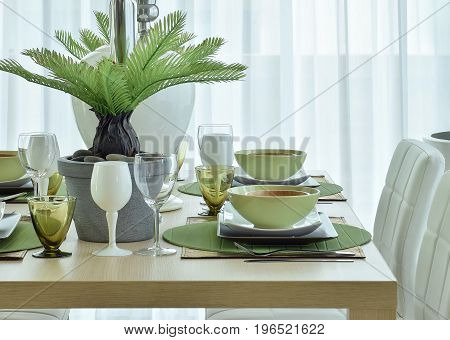 Modern Ceramic Tableware In Green Color Scheme Setting On Wooden Dining Table