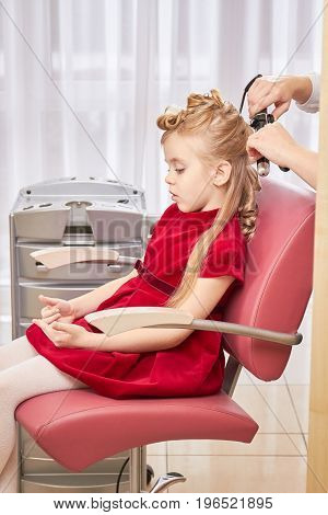Little caucasian girl, hair salon. Hands of stylist, curling iron.