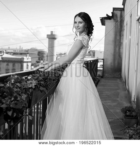 Young pretty stylish bride in fluffy white dress. Beautiful young woman with hairstyle and make up standing close to guardrail at terrace