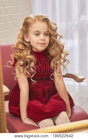 Little girl with beautiful hair. Caucasian child sitting indoor. Special occasion hairstyles for kids.