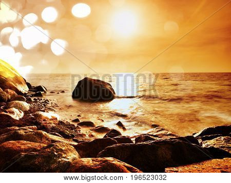Film Effect. Boulders At Island Shore Stick Up From Smooth Sea. Stony Coast Defies To Waves Of Ocean