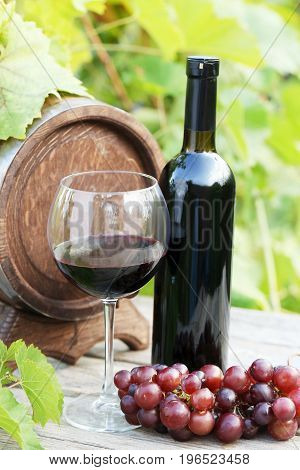 Wine In Glass With Bunch Of Grape On Wooden Table