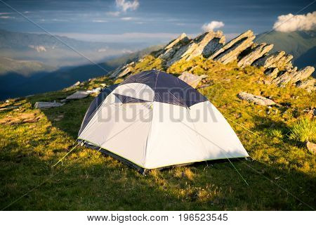 Tourist tent on a grass and next to the rocks. Tent in the mountains. Sunset. Holiday and summer time.