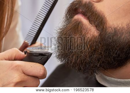 Beard trimming close up. Hand of barber with trimmer. How to shape a beard.