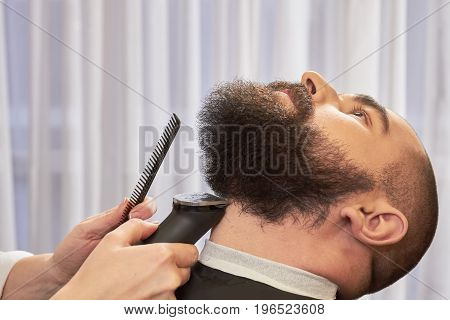Hand of barber trimming beard. Hands holding comb and trimmer.