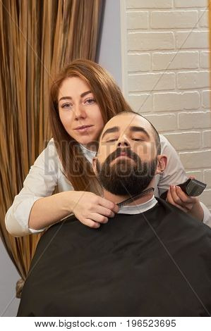 Barber holding trimmer and comb. Bearded caucasian man in barbershop. Barber training courses.