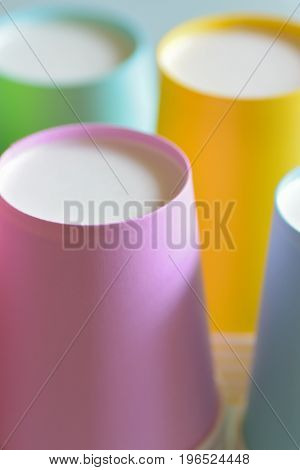 Macro details of lined up colorful paper cups in vertical frame