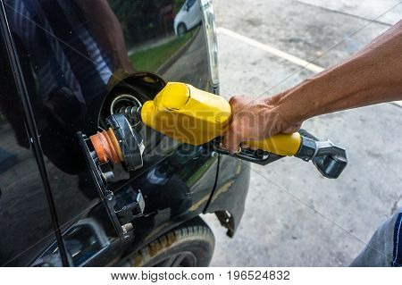 Asia man's hand holding nozzle & pumping gasoline fuel in car for refuelling gas at petrol station.