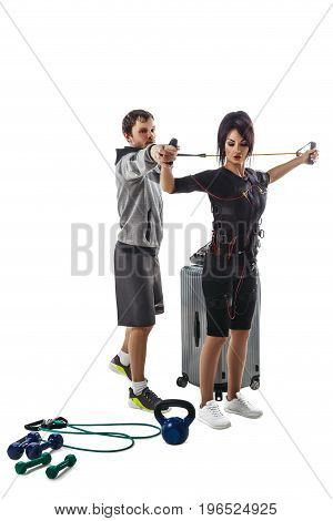Electrical muscular stimulation fitness woman in full ems suit doing chest crossfit exercise with training cable. Trainer helps her. Studio photo isolated on white background.