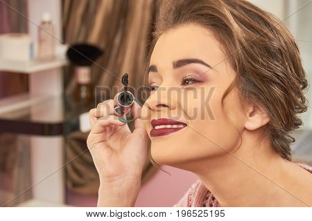 Woman applying makeup and smiling. Happy female using mascara. Fun facts about cosmetics.