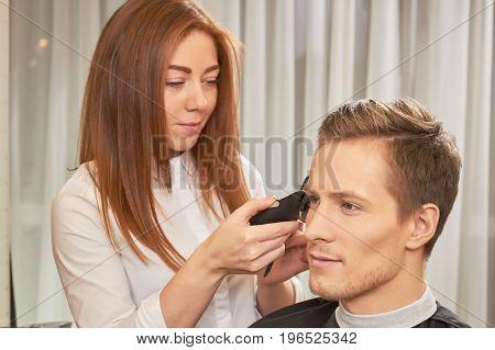Female barber using hair clipper. Male hair salon customer.