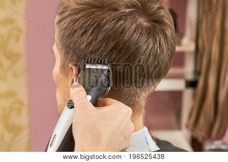 Hand of barber, hair clipper. Person getting haircut close up. Self sharpening steel blades.