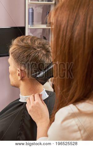 Barber and customer, blow dryer. Man in barbershop.