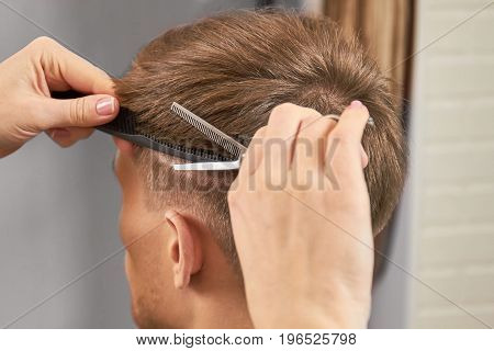 Hands of barber cut hair. Comb and scissors. Basic barbering techniques.
