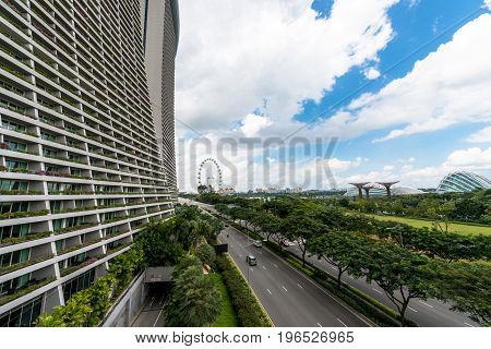SINGAPORE - MARCH 22 2017: Wide angle with of Gardens by the Bay Park Marina Bay Sands Hotel and Singapore Flyer in a cloudy day in Singapore