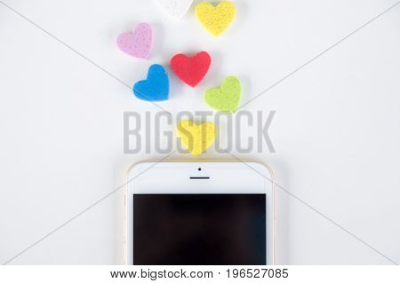 Colorful hearts sending out from smartphone on white background communication concept