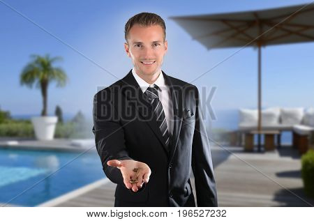 Handsome real estate agent in front of luxury villa with real-estate agent