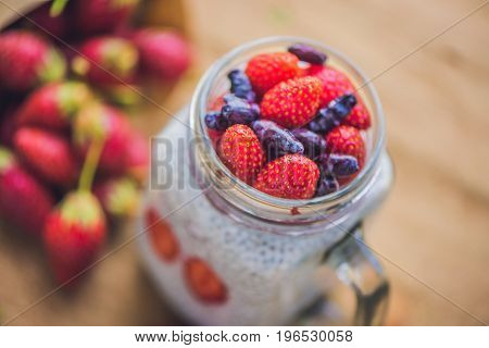 Healthy Layered Dessert With Chia Pudding, Strawberry And Honeysuckle In A Mason Jar On Rustic Backg