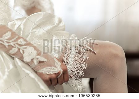 The bride puts on the garter at wedding
