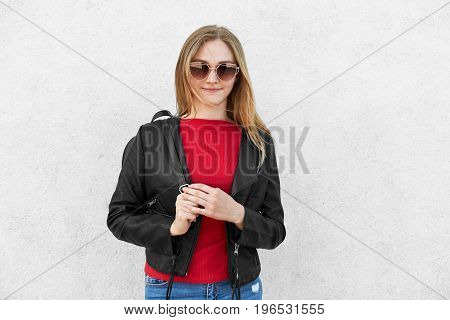 Horizontal Portrait Of Fashionable Female Wearing Black Jacket, Red Sweater And Trendy Sunglasses Ha
