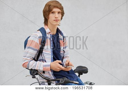 People, Travel, Technology, Leisure And Lifestyle Concept. Young Male Standing Near His Bike Holding
