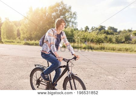 Handsome With Trendy Hairstyle Wearing Shirt And Jeans Having Backpack On Back Riding Bicycle On Roa
