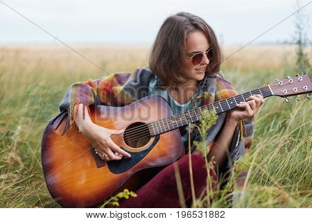 Young Female With Dark Short Hair Sitting At Green Grass Outdoors Playing Guitar Enjoying Nice Lands