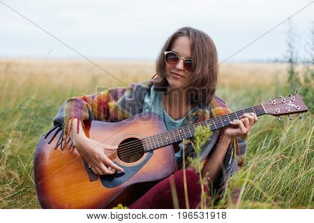 Outdoor Portrait Of Attractive Female With Dark Hair Wearing Sunglasses Playing Acoustic Guitar Demo