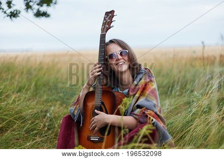 Talented Young Female Dressed Casually Holding Guitar Smiling Broadly At Camera Having Good Mood To