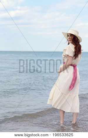 vintage redhead woman wearing hat at the ocean