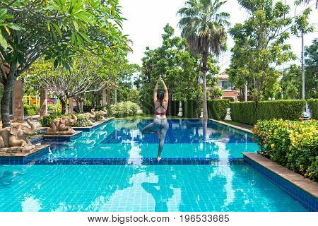 Asia woman doing yoga fitness exercise for relax and healthy beside swimming pool background. Healthy Concept.