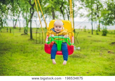 Happy Little Boy Riding On A Swing In A Park