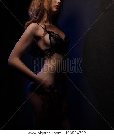Sexy Young Beautiful Woman With Curls In Sensual Black Lingerie, Lighted With Blue In Studio, One Si