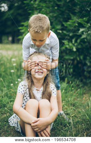 kids playing in the park, guess who, closing each other eye, siter and brother