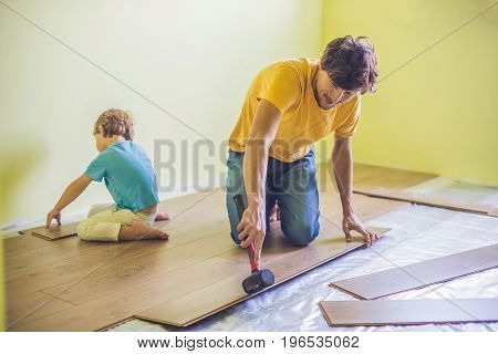 Father And Son Installing New Wooden Laminate Flooring. Infrared Floor Heating System Under Laminate