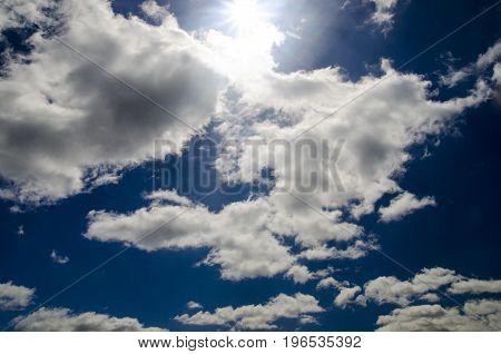 Sun in the deep blue sky beautiful clouds and sun rays
