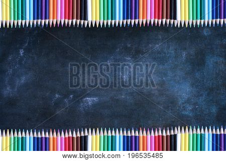 Dusty blank school chalkboard or blackboard and colored pencils with room for copy space.