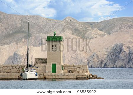 lighthouse and sailingboat in Baska, island Krk, Croatia