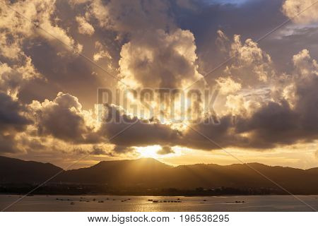 Sunset with sky clouds over mountain and andaman sea at phuket thailand.
