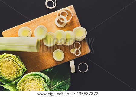 Cooking healthy food background. Cutting leek, fresh organic vegetables on black. Natural food with copy space.