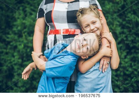 grandmother hugs granddaughter and grandson in the park
