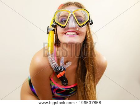 Woman wearing swimsuit with snorkeling mask having fun studio shot Happy joyful girl dreaming about active summer vacation. Snorkeling swimming concept
